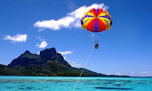 Dù lượn là môn thể thao mạo hiểm được vận hành bằng sức gió do ca nô kéo. Trong trò chơi này, bạn sẽ được treo lơ lửng ở độ cao 70-100 m để chiêm ngưỡng biển từ trên cao. Ảnh: Greenadventure.