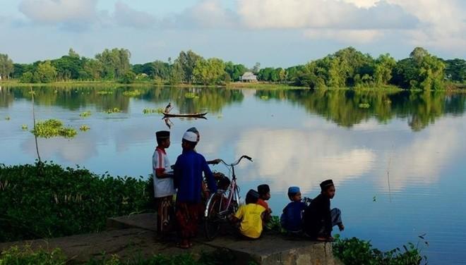 Bọn trẻ ở làng người Chăm vui đùa bên hồ nước trời ban. Ảnh: Nam Chấy.