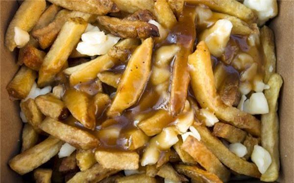 <strong>Poutine (Canada): </strong> Poutin là món ăn vặt phổ biến trên các đường phố của Canada, đặc biệt là ở Québec. Món ăn này gồm khoai tây chiên thấm đẫm nước thịt và phô mai.