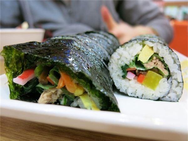 <strong>Cơm cuộn Gimbap (Hàn Quốc): </strong> Phần nhân Gimbap thường được làm từ thịt cua, trứng, thịt bò, cà rốt, cuộn chặt trong cơm và rong biển. Bạn có thể thưởng thức món này ở Seoul, nơi Gimbap được bán ở các cửa hàng và quầy ăn khắp thành phố.
