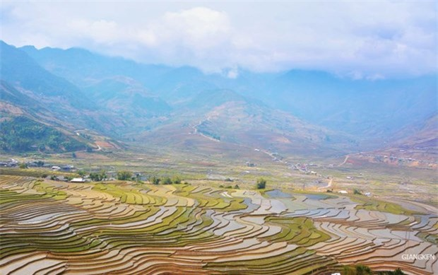 Những thửa ruộng loang loáng nước trải dài dưới chân những ngọn núi cao xanh tím, bên trên là mây trắng vờn quanh