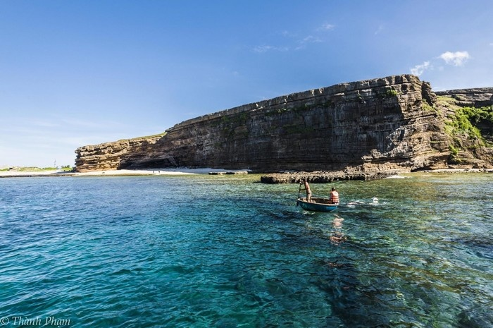 Du khách có thể ngồi thuyền thúng để dạo chơi trên mặt biển trong vắt - Ảnh: Thành Phạm